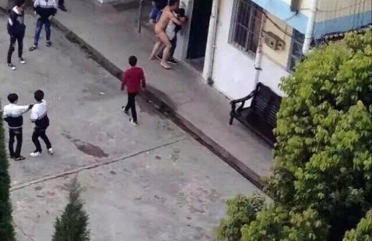 "Pic shows: Hou attempts to ërapeí the victim. Shocking photos have emerged from a Chinese high school where one of the faculty members stripped naked and attempted to rape a female pupil. The now viral photos show the employee, reportedly mentally ill, in the nude, bear-hugging the victim from behind while shocked pupils watch on in horror. Reports from Lingshan County, in South Chinaís Guangxi Zhuang Autonomous Region, said that the 30-year-old suspect, surnamed Hou, worked as a caretaker for Taiping Middle Schoolís laboratories. Hou is said to have stormed out of a school building unclothed, after which he picked out a female pupil at random and began ëharassingí her. As at least six other schoolboys stood watching in shock, Hou pushed the victim against the exterior wall of a classroom while she screamed for help. Nearby teachers soon intervened and helped subdue Hou, who had been employed by the high school for a number of years. Local authorities then detained Hou, who reportedly has a history of suffering mental illness. The specifics of Houís illness were not mentioned in reports. A police spokesman said: ""The suspect appears to have been suffering from mental disorders since 2011, but doctors said he would have been fine if the illness had not returned in two years."" The victim reportedly did not suffer any physical pain, but will be referred to a psychiatrist for possible emotional and psychological trauma. It is as of yet unclear whether Hou will be immediately relieved of his position at the school following the incident. (ends)"