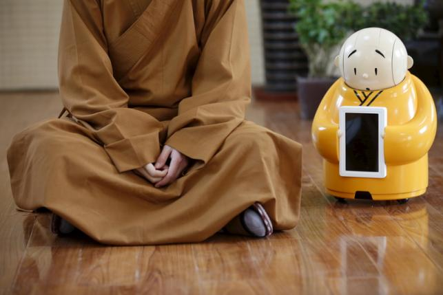 Robot Xian'er is placed next to Master Xianfan while Xianfan has an interview with Reuters at  Longquan Buddhist temple on the outskirts of Beijing, April 20, 2016.  REUTERS/Kim Kyung-Hoon